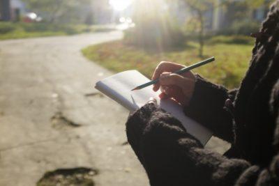 紙に書いている人の画像